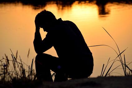 Mann sitzt depressiv am Ufer eines Wassers