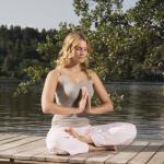 Meditierende auf Holzsteg im See